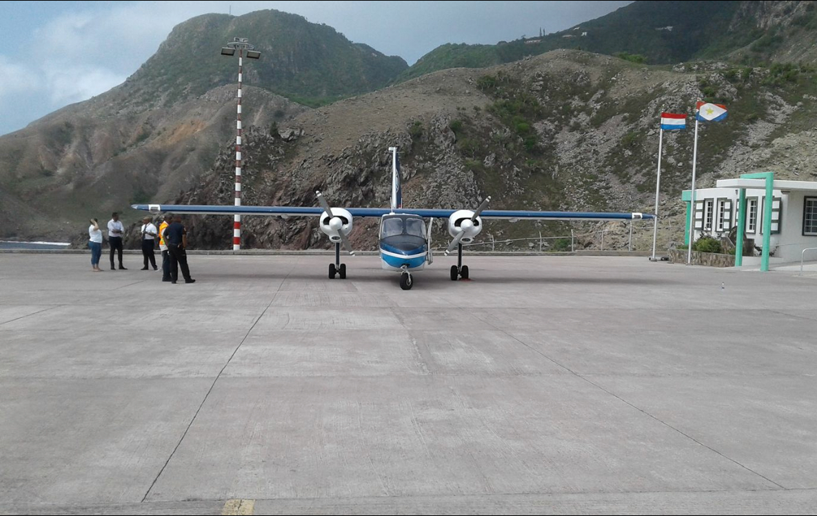 SXM Airways BN Islander aircraft parked at Saba Airport with pilot pax - front view