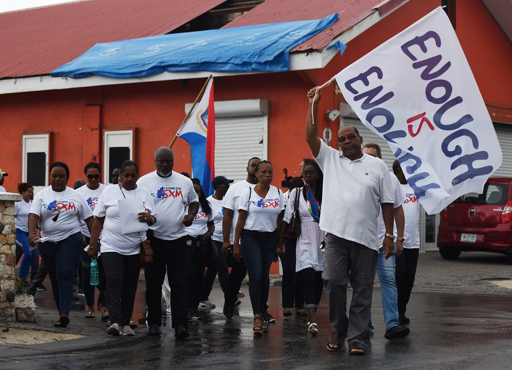 Protesters, including educator Roberto Arrindell, march through Philipsburg, waving flags.