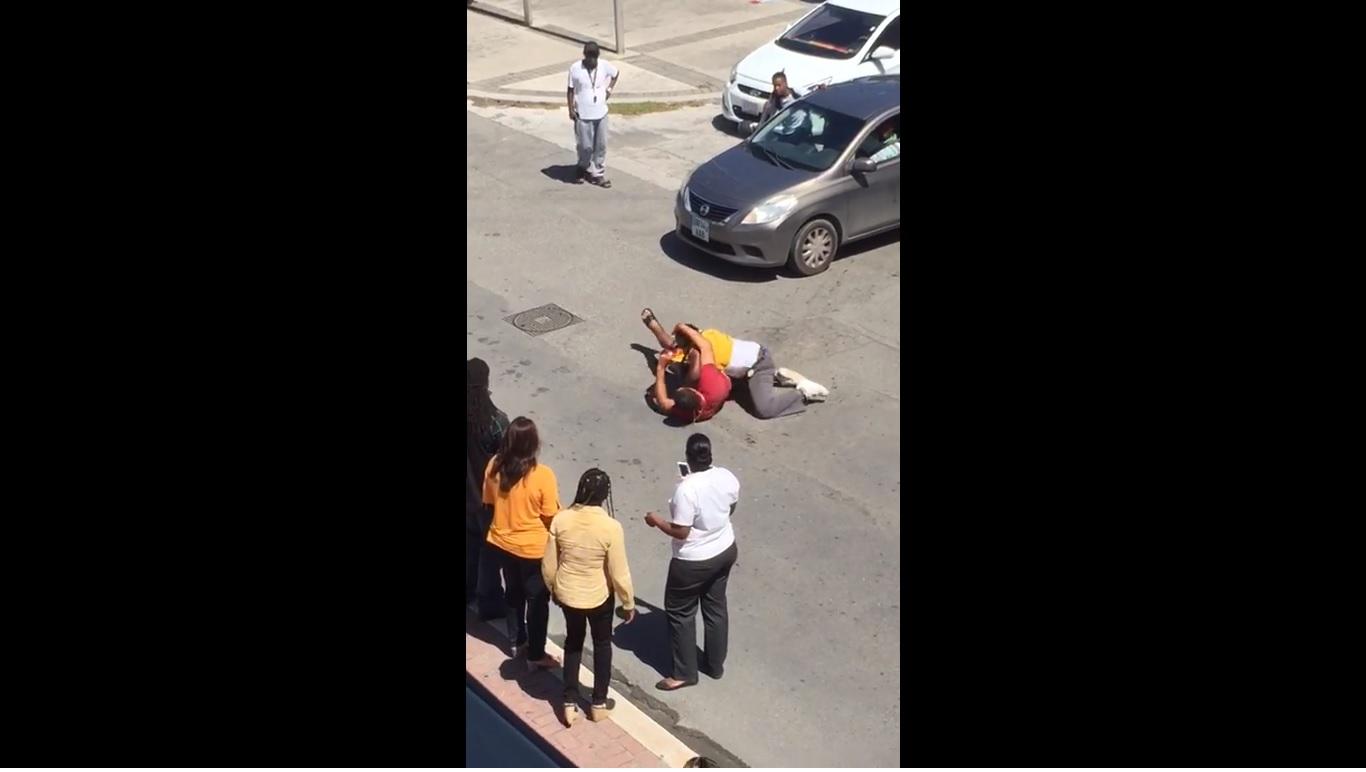 Screenshot men fighting in public on street