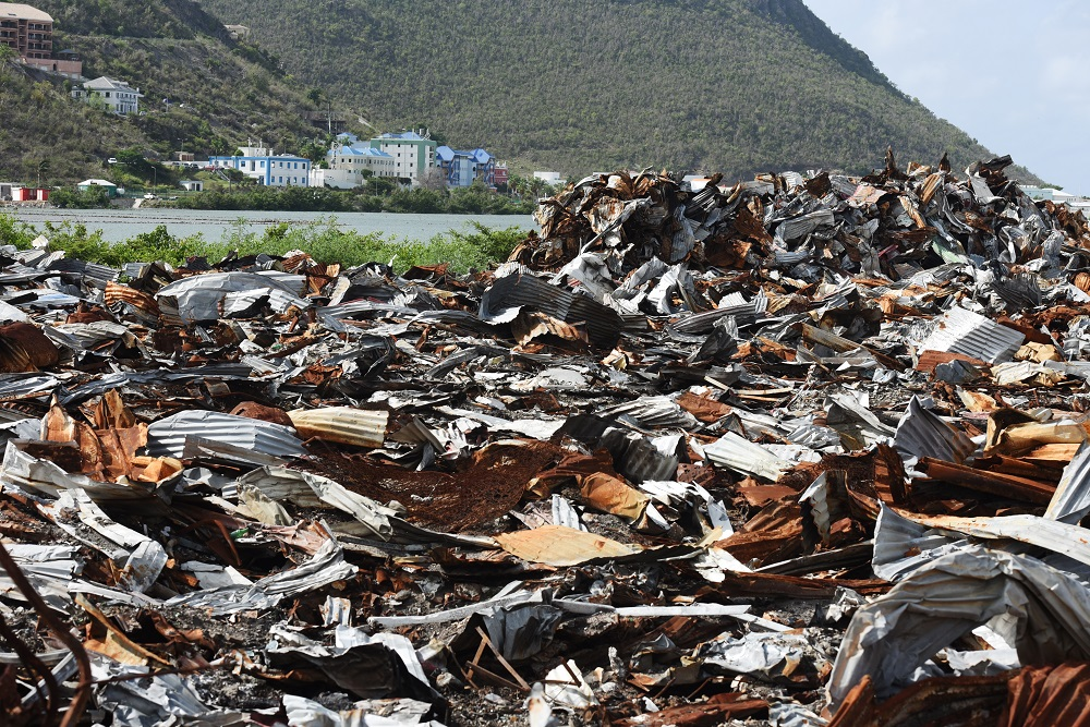 Thousands of sheets of galvanized zinc lies twisted and charred from numerous fires at the dumping grounds on Pond Island. (D.A. Robin/Photojournalist)